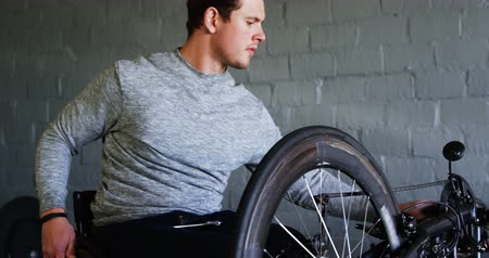 challenged : Young disabled man repairing wheelchair at workshop 4k Stock Footage