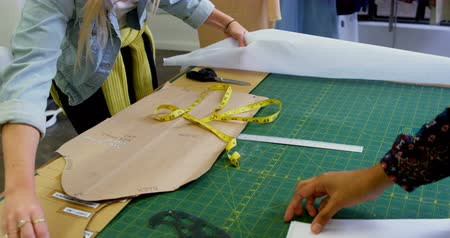 навыки : Fashion designers working on table in fashion studio 4k Стоковые видеозаписи