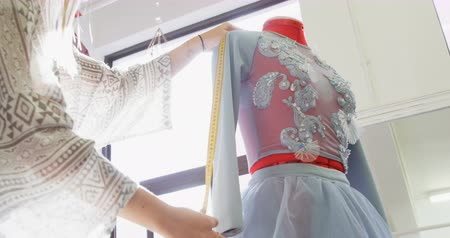 projektant : Fashion designer measuring dress on dressmakers model in fashion studio 4k