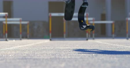 physically : Low section of disabled athletic standing on a running track 4k