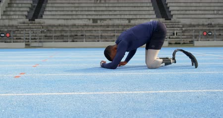 ajoelhado : Disabled athletic relaxing on a running track at sports venue 4k Stock Footage