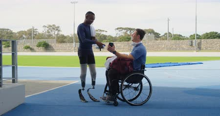 amputee : Two disabled athletics discussing over mobile phone at sports venue 4k