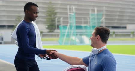 physically : Two disabled athletics interacting with each other at sports venue 4k
