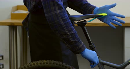 szerelő : Mid section of man repairing bicycle seat in workshop 4k Stock mozgókép