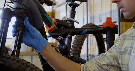 mend : Close-up of man repairing bicycle in workshop 4k