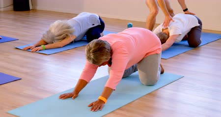 senior lifestyle : Trainer assisting senior women in performing yoga at yoga center 4k