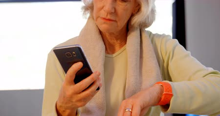 active ageing : Senior women using mobile phone and smartwatch in yoga center 4k Stock Footage