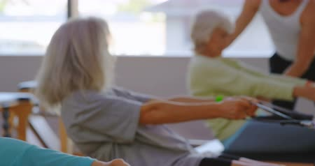 active ageing : Trainer assisting senior women while stretching exercise in yoga center 4k
