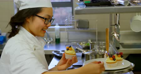 internat : Smiling female chef garnishing muffins in kitchen at restaurant 4k