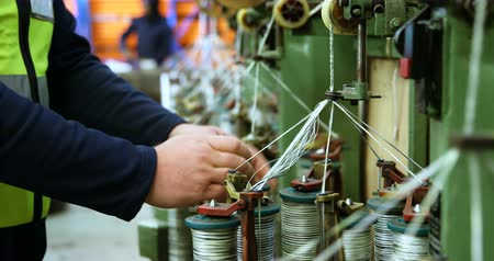 производитель : Mid section of worker working in rope making industry 4k