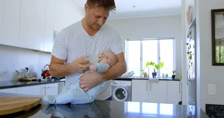 ev hayatı : Father feeding milk to his baby boy in kitchen at home 4k Stok Video