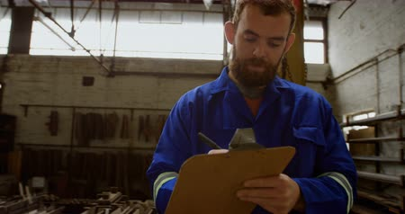 inventario : Attentive metalsmith writing on clipboard in workshop 4k Archivo de Video