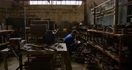 inventario : Metalsmith maintaining stocks on digital tablet in workshop 4k