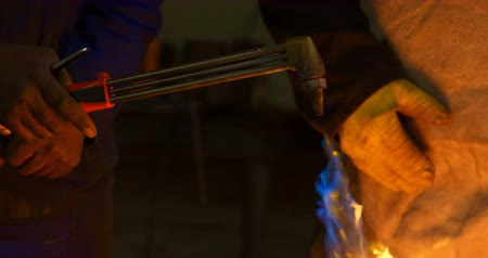 welding torch : Two metalsmiths lighting welding torch in workshop 4k Stock Footage