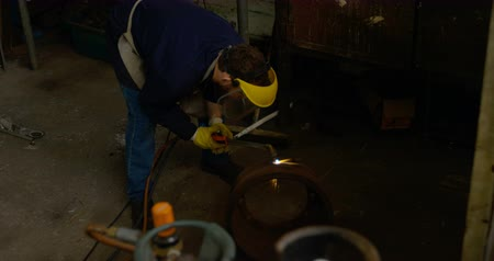 colegas de trabalho : Attentive metalsmith using welding torch in workshop 4k