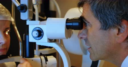 gepensioneerd : Optometrist examining patient eyes with slit lamp in clinic 4k