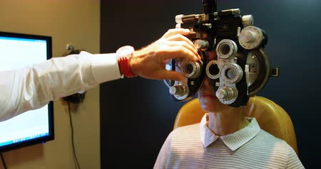 phoropter : Optometrist examining patient eyes with phoropter in clinic 4k Stock Footage