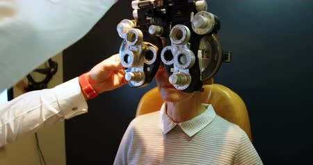 czek : Optometrist examining patient eyes with phoropter in clinic 4k Wideo