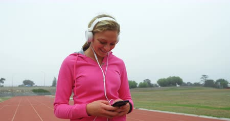 high speed track : Young female athlete listening music on mobile phone at sports venue 4k Stock Footage