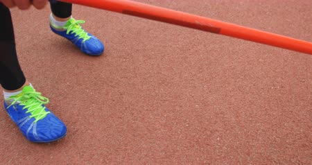 javelin : Low section of female athlete holding javelin throw at sports venue 4k Stock Footage