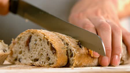 cutting up : Close-up of woman cutting loaf of bread 4k Stock Footage