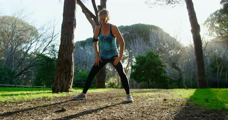 warming up : Active senior woman exercising in the park 4k
