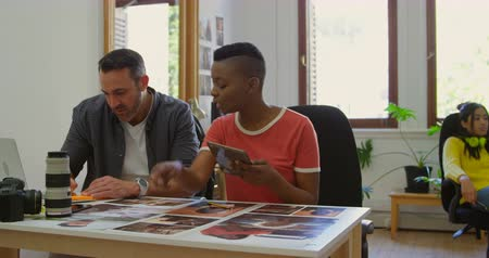 colegas de trabalho : Business colleagues discussing over photographs at desk in office 4k