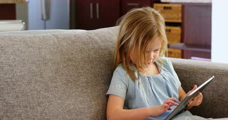 görgetés : Girl using digital tablet in living room at office 4k