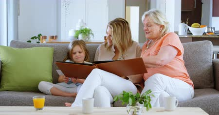 homely : Family looking photo album in living room at home 4k Stock Footage