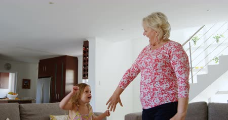 active ageing : Grandmother and granddaughter dancing in living room at home 4k Stock Footage