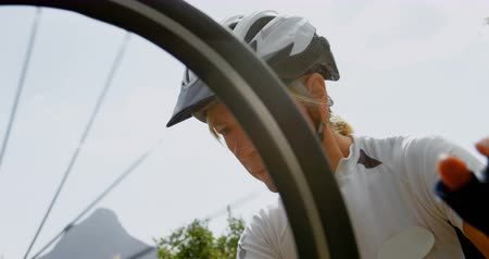 ciclista : Active senior cyclist checking bicycle at countryside 4k