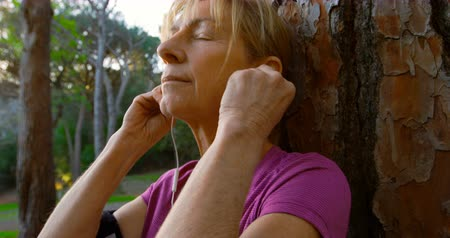 active ageing : Active senior woman leaning on a tree and listening music 4k Stock Footage
