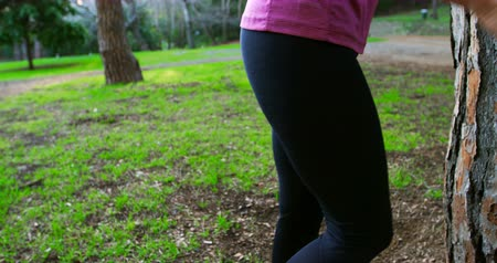 escuta : Low section of senior woman exercising in the park 4k Vídeos