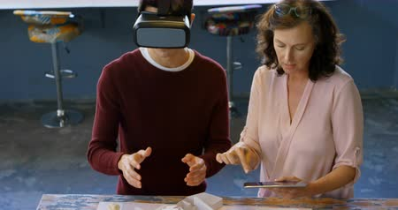 helft : Executives using digital tablet and virtual reality headset while discussing over architectural model in the office 4k