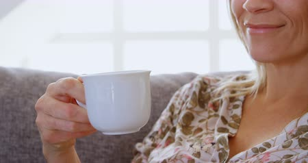 mid section : Close-up of woman having coffee on sofa at home 4k