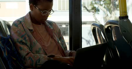 busz : Young female commuter using laptop while travelling in bus 4k
