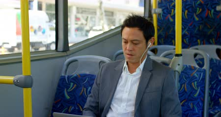 身なり : Male business commuter listening music on laptop while travelling in bus 4k 動画素材