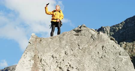 active ageing : Senior woman taking selfie with mobile phone on a rock at countryside 4k Stock Footage