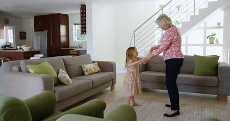 homely : Grandmother and granddaughter dancing in living room at home 4k Stock Footage