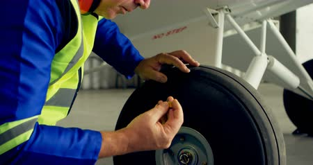 earmuffs : Engineer reparing aircraft wheel at aerospace hangar 4k Stock Footage