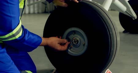 earmuffs : Engineer fixing a wheel of aircraft in hangar 4k