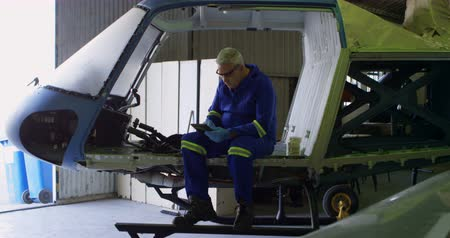 görgetés : Male engineer using digital tablet in aircraft hangar 4k