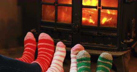 ev gibi : Low section of family relaxing near fireplace at home 4k Stok Video