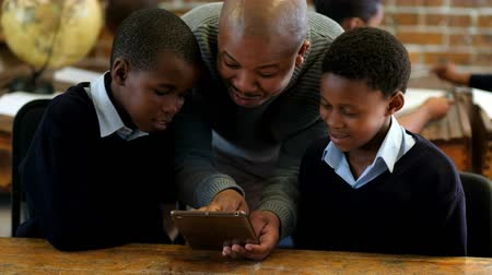estudioso : Male teacher using digital tablet with students in classroom at school 4k