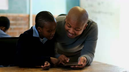 estudioso : Male teacher using digital tablet with student in classroom at school 4k