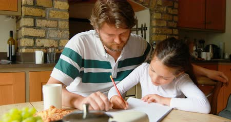 ev gibi : Father helping daughter in studies in kitchen at home 4k