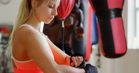 energický : Young female boxer wearing hand wrap in fitness studio 4k