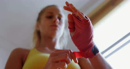 életerő : Young female boxer wearing hand wrap in fitness studio 4k