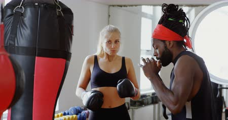 punching bag : Male trainer assisting female boxer in fitness studio 4k