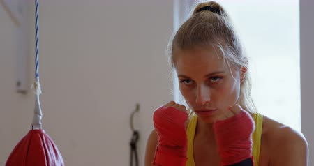 punching bag : Young female boxer practicing boxing in fitness studio 4k